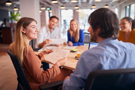 Business Team Having Meeting Sitting Around Table In Modern Open Plan Office