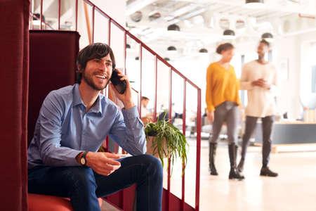 Businessman On Phone Sitting By Stairs In Modern Open Plan Office Foto de archivo