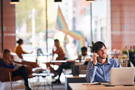 Businessman Sitting At Desk On Phone Call In Modern Open Plan Office