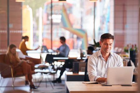 Businessman Sitting At Desk Working On Laptop In Modern Open Plan Office
