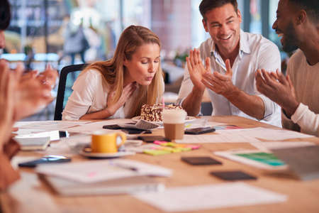 Colleagues Celebrating Businesswoman's Birthday At Meeting Around Table In Modern Open Plan Office