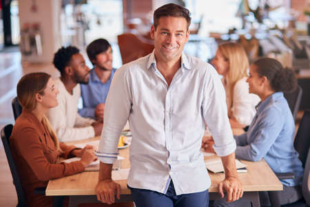 Portrait Of Businessman With Colleagues In Background Sitting Around Table In Open Plan Office