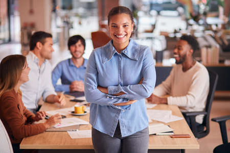 Portrait Of Businesswoman With Colleagues In Background Sitting Around Table In Open Plan Office Foto de archivo