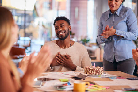 Colleagues Celebrating Businessman's Birthday At Meeting Around Table In Modern Open Plan Office