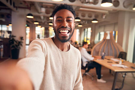 Portrait Of Young Businessman Taking Selfie On Mobile Phone In Modern Open Plan Office Foto de archivo
