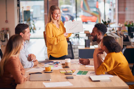 Businesswoman Giving Presentation To Colleagues Sitting Around Table In Modern Open Plan Office