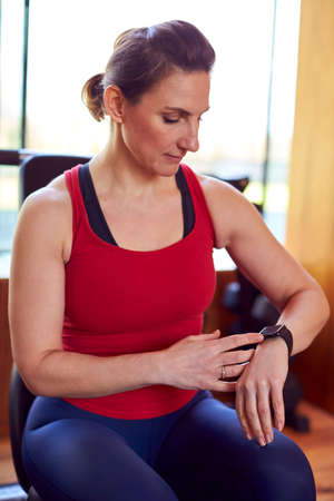 Mature Woman Exercising In Home Gym Checking Health App On Smart Watch Foto de archivo
