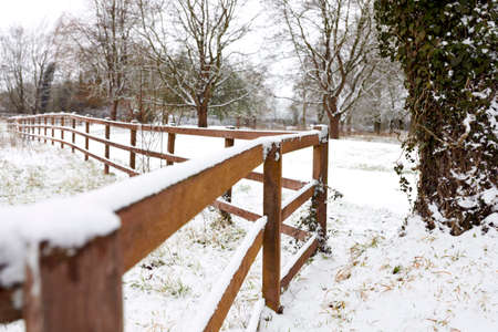 Close Up Of Snow Covered Fence Beside Field In Countryside