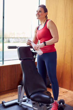 Mature Woman Exercising In Home Gym Taking A Break And Drinking Water