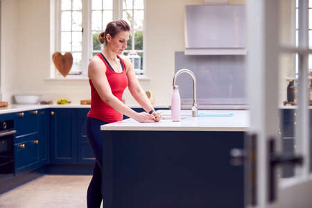 Mature Woman Wearing Fitness Clothing Checking Messages At Home In Kitchen After Exercising Foto de archivo