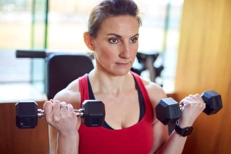 Mature Woman Exercising In Home Gym Lifting Hand Weights