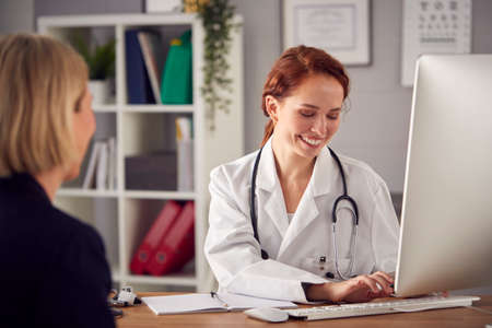 Female Doctor In White Coat Having Meeting With Mature Woman Patient In Office