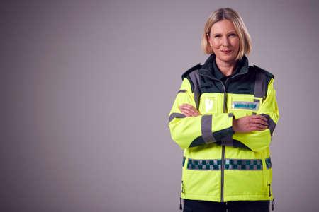 Studio Portrait Of Smiling Mature Female Paramedic Against Plain Background