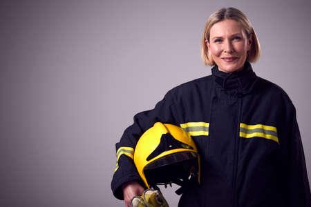 Studio Portrait Of Smiling Mature Female Firefighter Holding Helmet Against Plain Background