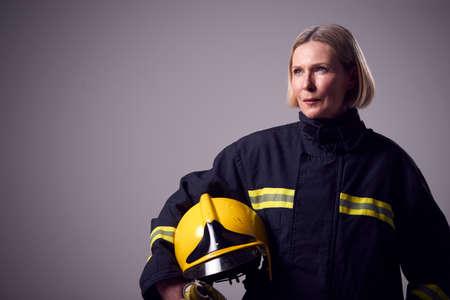 Studio Portrait Of Serious Mature Female Firefighter Holding Helmet Against Plain Background