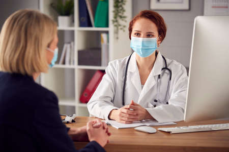 Female Doctor In White Coat Wearing Face Mask Having Meeting With Mature Woman Patient In Office Foto de archivo