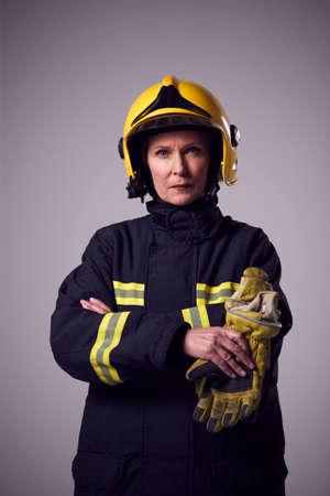 Studio Portrait Of Serious Mature Female Firefighter Against Plain Background Foto de archivo