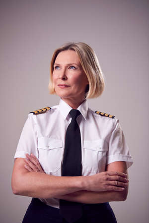 Studio Portrait Of Serious Mature Female Airline Pilot Against Plain Background Foto de archivo