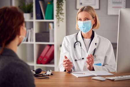 Mature Female Doctor In White Coat Wearing Face Mask Having Meeting With Woman Patient In Office