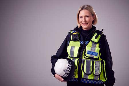 Studio Portrait Of Smiling Mature Female Police Officer Holding Hat Against Plain Background