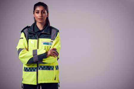 Studio Portrait Of Serious Young Female Paramedic Against Plain Background Foto de archivo