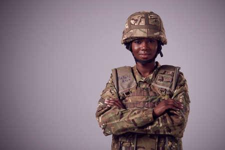 Studio Portrait Of Smiling Young Female Soldier In Military Uniform Against Plain Background Foto de archivo