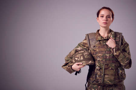 Studio Portrait Of Serious Young Female Soldier In Military Uniform Against Plain Background
