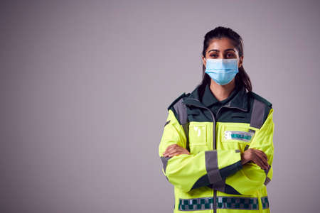 Studio Portrait Of Young Female Paramedic Wearing Face Mask Against Plain Background