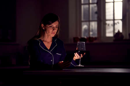 Unhappy Woman Wearing Pyjamas Sitting In Kitchen With Glass Of Wine At Night Using Mobile Phone