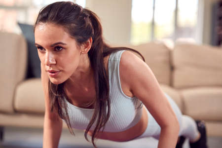 Woman In Fitness Clothing At Home In Lounge Doing Press Ups And Exercising With Hand Weights Standard-Bild