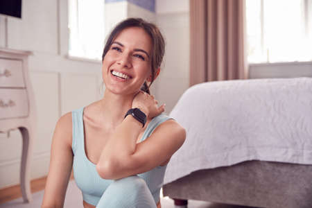Woman Wearing Fitness Clothing And Activity Monitor Sitting On Floor In Bedroom At Home