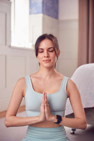 Woman Doing Yoga Wearing Fitness Clothing And Activity Monitor Sitting On Floor In Bedroom At Home