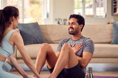Man With Female Personal Trainer Doing Sit Ups As Part Of Exercising At Home Standard-Bild
