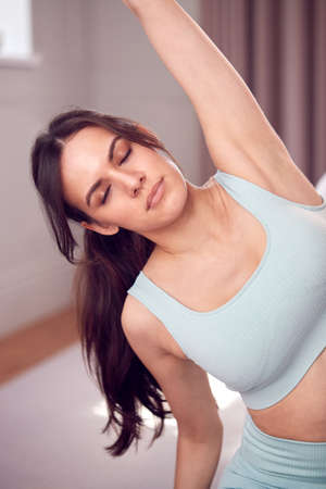 Woman Doing Yoga Wearing Fitness Clothing Sitting On Floor In Bedroom At Home Standard-Bild