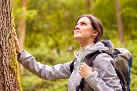 Woman Hiking Along Path Through Forest In Countryside Taking A Break And Resting Against Tree