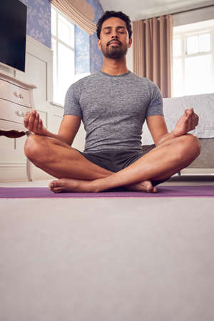Man Wearing Fitness Clothing In Bedroom At Home Sitting On Yoga Mat And Meditating