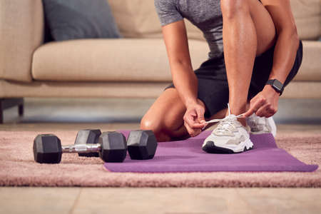 Close Up Of Man In Fitness Clothing At Home Fastening Trainers Before Exercising With Hand Weights Standard-Bild