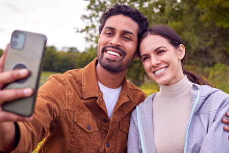 Couple On Walk In Countryside Taking Selfie On Mobile Phone