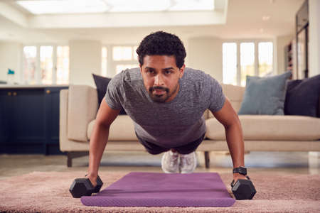 Man In Fitness Clothing At Home In Lounge Exercising With Hand Weights Standard-Bild