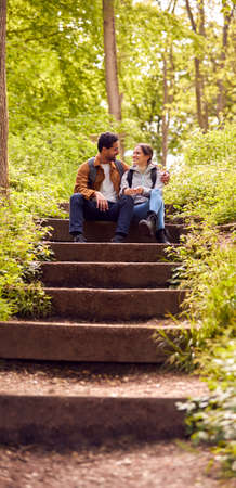 Hiking Couple With Backpacks Sitting On Steps On Path Through Trees In Countryside Together Standard-Bild