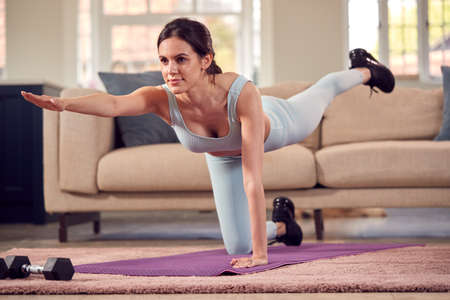 Woman In Fitness Clothing At Home In Lounge Doing Stretches And Exercising With Hand Weights Standard-Bild