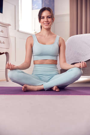 Portrait Of Woman Wearing Fitness Clothing In Bedroom At Home Sitting On Yoga Mat And Meditating