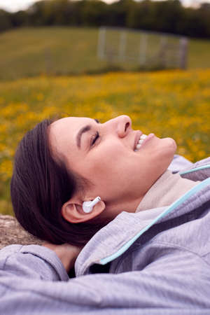 Woman Lying On Bench In Countryside Relaxing And Listening To Music Or Podcast On Wireless Earphones