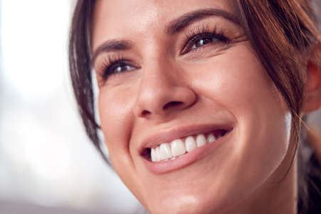 Close Up Portrait Of Relaxed And Natural Looking Woman Smiling At Home Standard-Bild