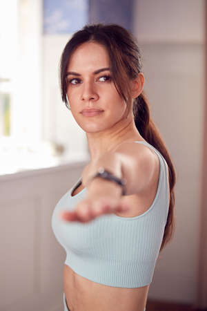 Woman Doing Yoga Wearing Fitness Clothing And Activity Monitor Stretching In Bedroom At Home
