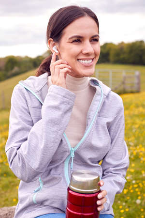 Woman Sitting On Bench In Countryside Relaxing And Listening To Music Or Podcast On Earphones