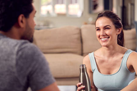 Woman With Male Personal Trainer Exercising At Home Together Standard-Bild