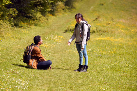 Couple With Backpacks Taking A Break On Hike Along Path Across Field By Forest In Countryside