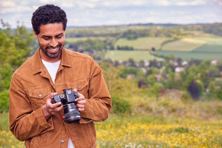 Man With Digital DSLR Camera Taking Photos In Countryside