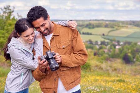 Couple With Digital DSLR Camera Taking Photos In Countryside Together